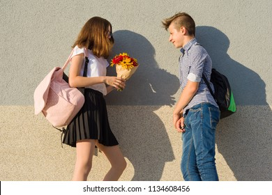 Boy gives girl bouquet of flowers. Outdoor portrait of couple teenagers