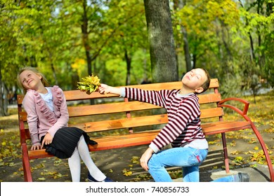 The boy gives the girl flowers from the autumn leaves to the bench in the park