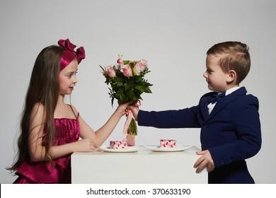 boy gives a girl flowers.little beautiful couple.kids love