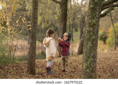 Boy giving beautiful girl flowers near lake