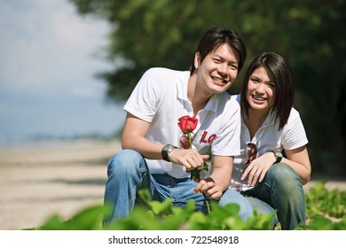 boy giving beautiful rose to his pretty girlfriend