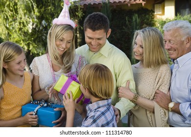 Boy giving gift to mother on her birthday