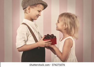 Boy giving a girl box full of chocolates