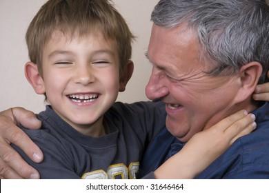 Boy giving his grandfather a huge hug
