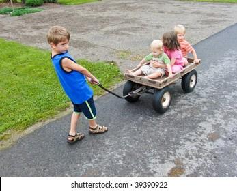 boy giving his siblings wagon rides