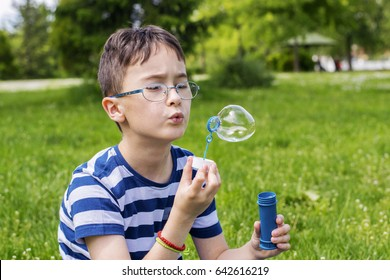 Boy with glasses blowing bubbles