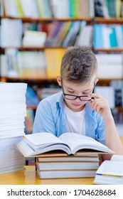 A boy with glasses in the library is studying. There are stacks of books near the student and he reads with his glasses down. Exam Preparation Concept