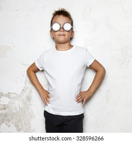 Boy with glasses stands on a wall background and smiling