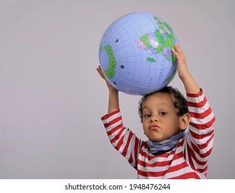 boy with globe on grey background stock photo