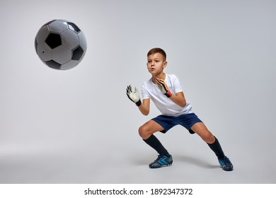 boy goalkeeper is catching soccer ball in air isolated on gray background, sport, play football, health, healthy lifestyle concept