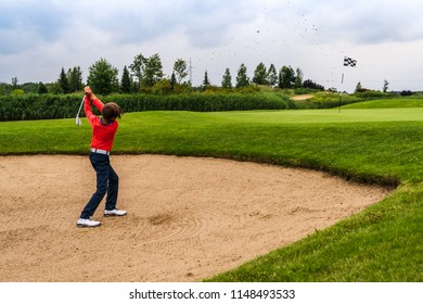 Boy golf player chipping from sand bunker onto green