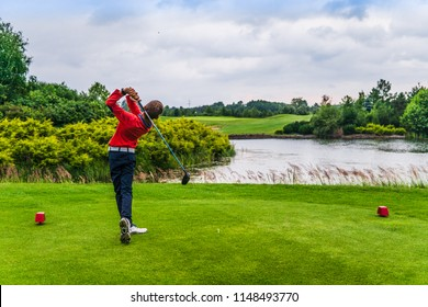 Boy golf player hitting golf ball over water from fairway onto green at golf course