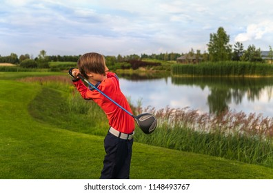 Boy golf player hitting by driver from fairway at golf course