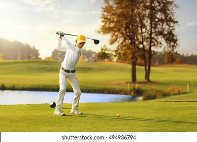 Boy golf player hitting by iron from fairway at autumn evening