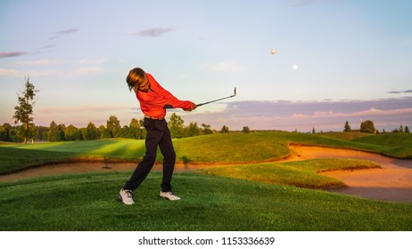 Boy golf player hitting chipping golf ball at golf course at the evening