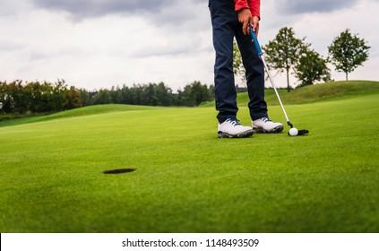 Boy golf player putting golf ball onto green