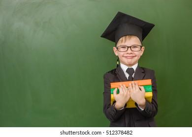 Boy in graduation cap with books standing near green chalkboard