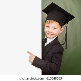 Boy in graduation hat pointing at blank placard.