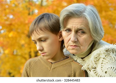 boy with grandmother in yellow autumn park