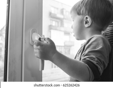 The boy grasps the handle of the window. A small child holding the handle of the window with the key.