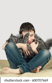 Boy with a gray cat on a white background