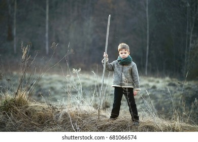 a boy in a gray jacket and black pants, with a stick in the field woods at sunset