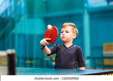boy in gray t-shirt playing table tennis, the moment of impact on the ball