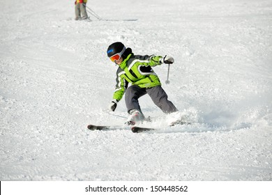 The boy in a green jacket on skis in mountains