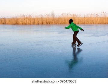 A boy in green jacket skates on the frozen river