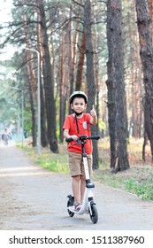 A boy in a green safety helmet rides a white scooter along a path in the forest. Bicycle helmet. Child athlete.