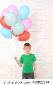 boy in green t-shirt holding a lot of colorful balloons against a white brick wall