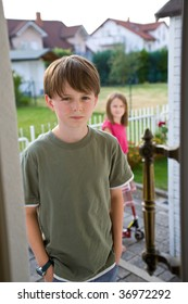 A boy in a green t-shirt stands in an open door with an angry, troubled expression on his face. His sister appears in the background.  The brother and sister have been arguing, and he is angry.