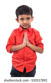 Boy greeting 'Namaste'. Kid Folded Hands Representing Traditional Indian Greeting, Namaste (Welcome), Isolated on White.