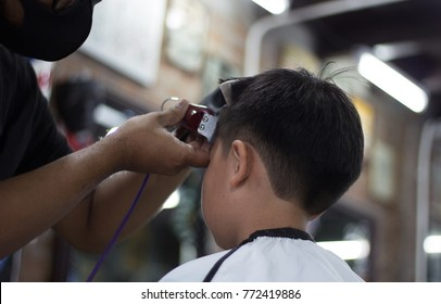 A boy is hair cutting with barber in the barbershop