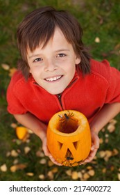 Boy with a Halloween pumpkin jack-o-lantern looking up