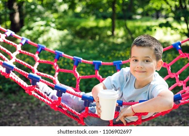 Boy in a hammock with a paper Cup of drink