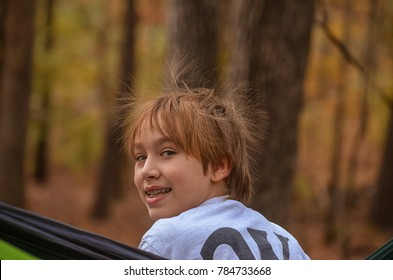 Boy in hammock with static hair in the fall