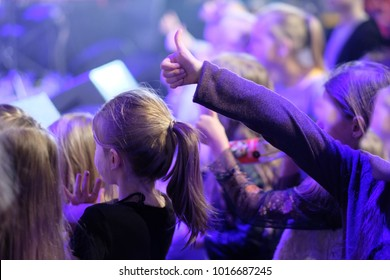 A boy with a hand up and an approving gesture with joyful emotions at a concert