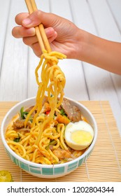 Boy hand holding chopsticks for eating Mee Rebus from white bowl on the table