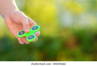 Boy hand holding trendy fidget spinner. Boy playing with green spinner outdoors  on the bright bokeh. Shallow DOF.