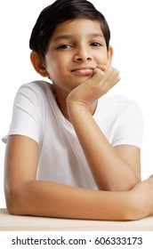Boy with hand on chin, looking at camera