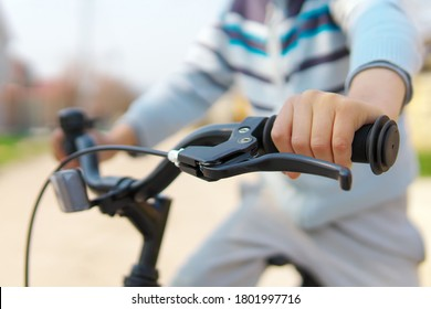 Boy hand on handlebar of bicycle at day.