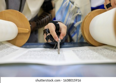 Boy Hand reading the Jewish Torah at Bar Mitzvah. Torah reading hand is a sacred tool used to point to the text during reading in the Torah scroll.