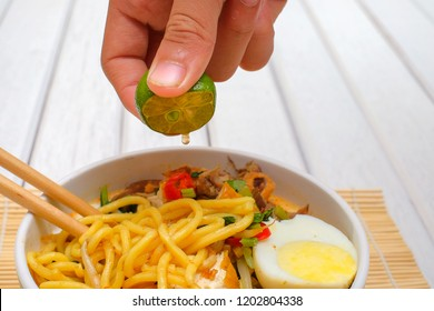 Boy hand squeezing lime on Malay Mee Rebus in the bowl  with chopsticks on white table This dish is made of noodles ,vegetable,egg with a spicy .