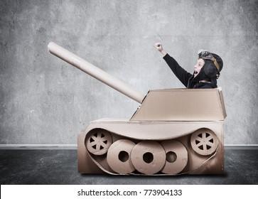 Boy in handmade cardboard panzer.
