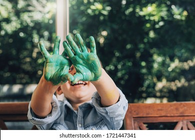 Boy with hands painted in green paints ready to make hand prints.