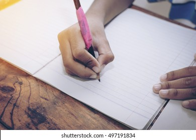 boy hands with pencil writing on notebook
