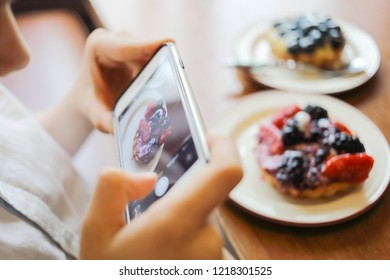 Boy hands in white shirt shoot cakes with smartphone on table, closeup