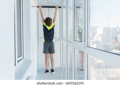 boy hang on horizontal bar on apartments balcony, doing sport exersise on quarantine, stay at home concept, self-isolation during pandemic of coronavirus