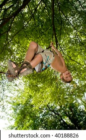 boy hanging from rope swing
